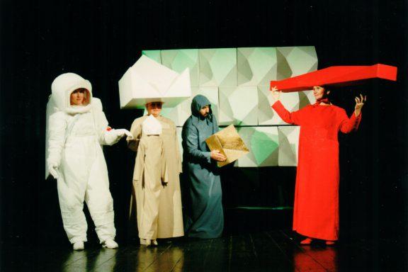 Aktorka w białym kostiumie kosmonauty, druga w białym 11-ściennym kapeluszu z bliźniaczą lalką, trzecia w czerwonym kostiumie i podłużnym K-dronie na głowie. W środku aktor z małym K-dronem. Z tyłu ściana z wielu K-dronów.