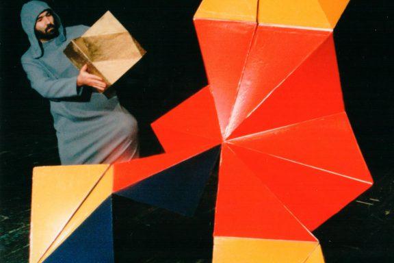 Aktor trzyma w rękach mały K-dron (11-ścienną bryłę), obok stoi duży kolorowy.