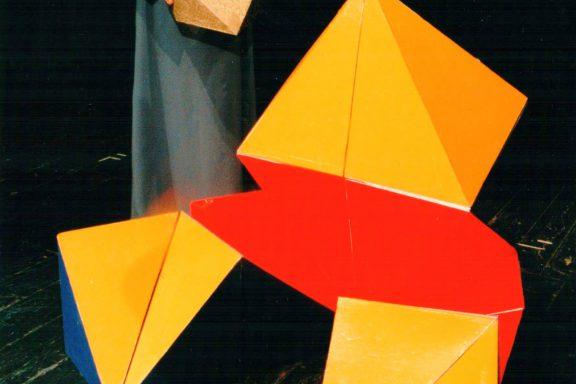Aktor trzyma w rękach mały K-dron (11-ścienną bryłę), obok rozkłada się duży kolorowy.