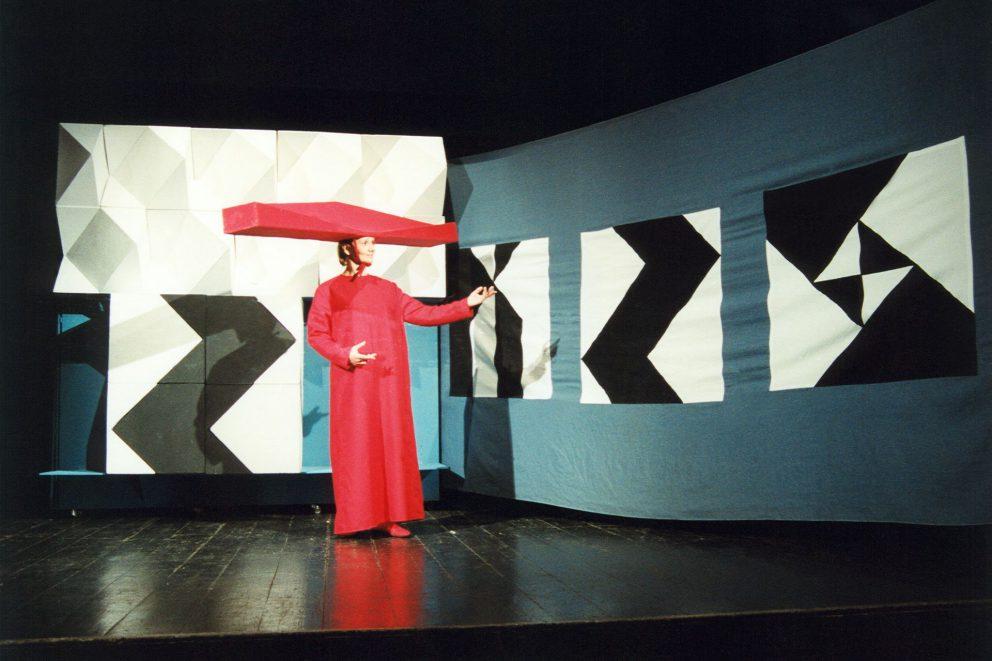 Aktorka w czerwonym kostiumie i kapeluszu w formie podłużnej bryły.