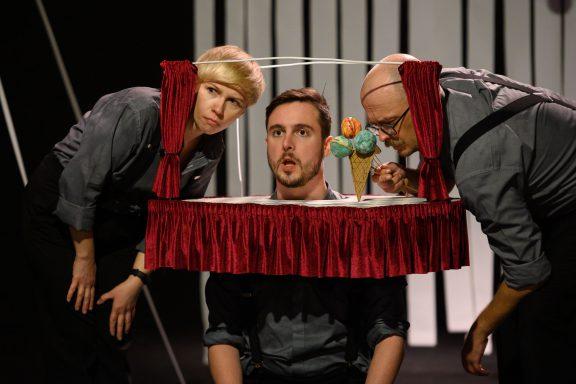 Trójka aktorów z głowami w mini scenie. Jeden z nich trzyma loda z trzema kolorowymi gałkami.