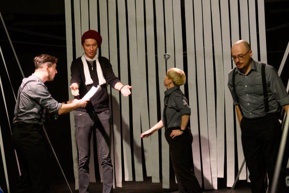 Trójka aktorów dyskutuje z reżyserem. Jeden z nich trzyma w ręku scenariusz.