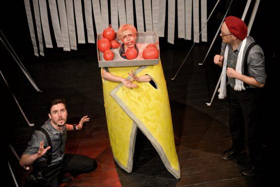 Aktorka z błagalną miną. Ma na szyi karton z czerwonymi kulami. Obok stoi dwójka aktorów z przerażonymi minami.