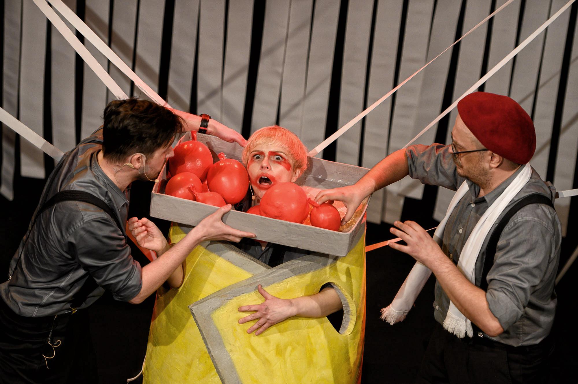 Aktorka z pomalowaną twarzą i przerażoną miną. Trzyma na szyi karton z czerwonymi kulami. Obok stoi pozostała dwójka aktorów.