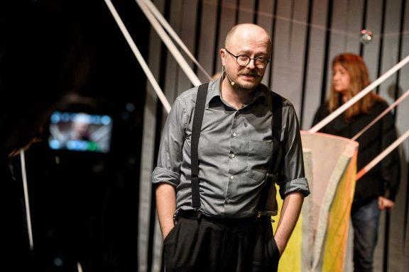 Aktor w okularach zwraca się do widza. W tle pozostali aktorzy.