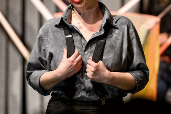 Aktorka z częściowo pomalowaną twarzą na czerwono.