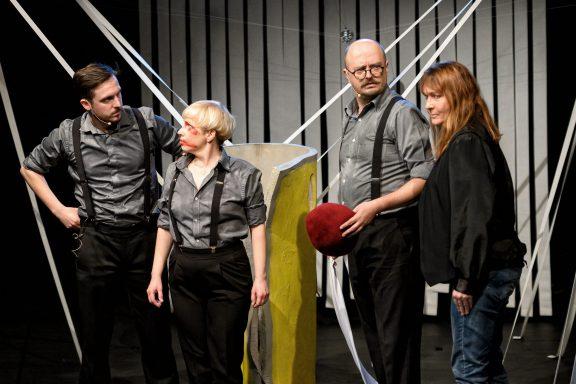 Czwórka aktorów stoi na scenie ze zdziwionymi minami.