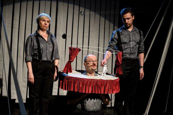 Trójka aktorów stoi na scenie. Jeden z nich animuje lalką na mini scenie.