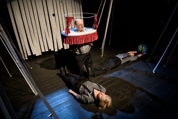 Dwoje aktorów leży na scenie. Jeden z nich trzyma w rękach globus.