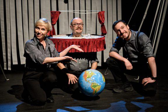 Aktorzy uśmiechają się. Jeden z nich prezentuje globus.