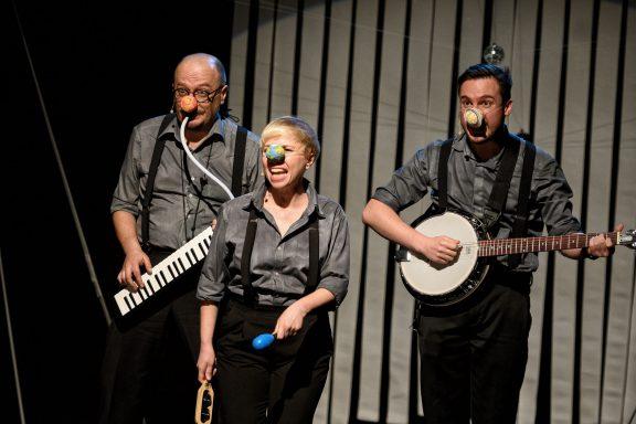 Trójka aktorów na scenie gra na różnych instrumentach.