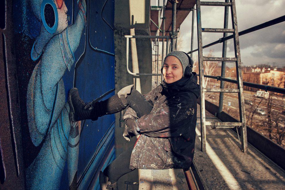 Fotografia przedstawia artystkę - Monę Tusz w trakcie wykonywania muralu.