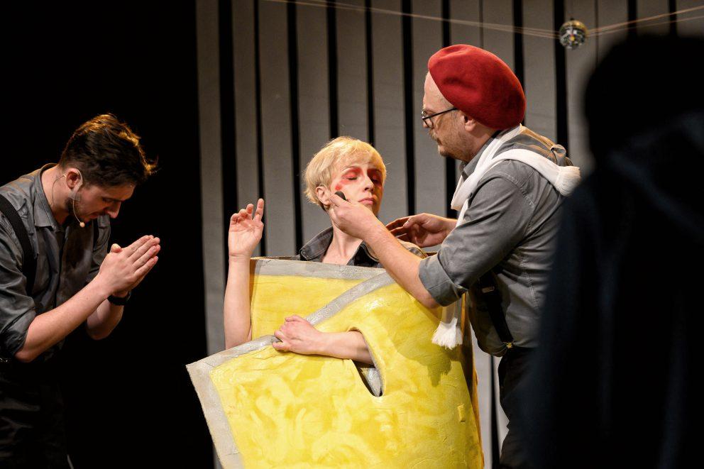 Aktor w czerwonym berecie, maluje twarz aktorki czerwoną farbą.