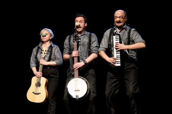 Trójka aktorów z instrumentami muzycznymi w ręku.